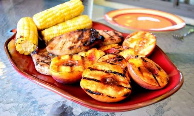 Spicy Grilled Pork Chops with Cinnamon Peaches and Corn on the Cob - Before your head out on your next family camping trip, you must check out these 26 camping recipes. We will want to try these family-friendly recipes ranging from main entrees to desserts and snacks. These meal ideas are sure to make your next campout a great success!