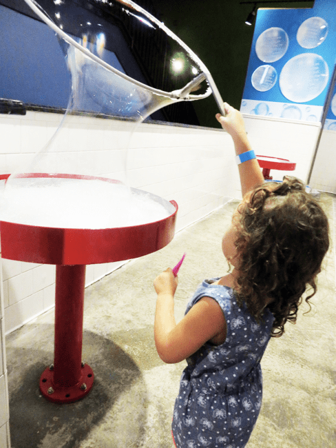 Girl playing with bubbles at Wonderworks